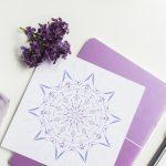 мандала в лилави цветове, кристал и люляк върху бяла маса